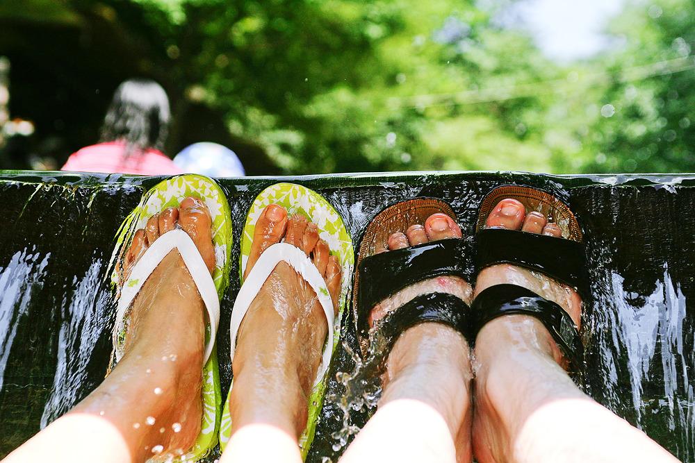 계곡에 누워 발을바라보며 촬영한 사진으로 신발신은 발 뒷편으로는 흐르는 계곡물과 서있는 사람들의 상체만 흐리게 나타나있다.